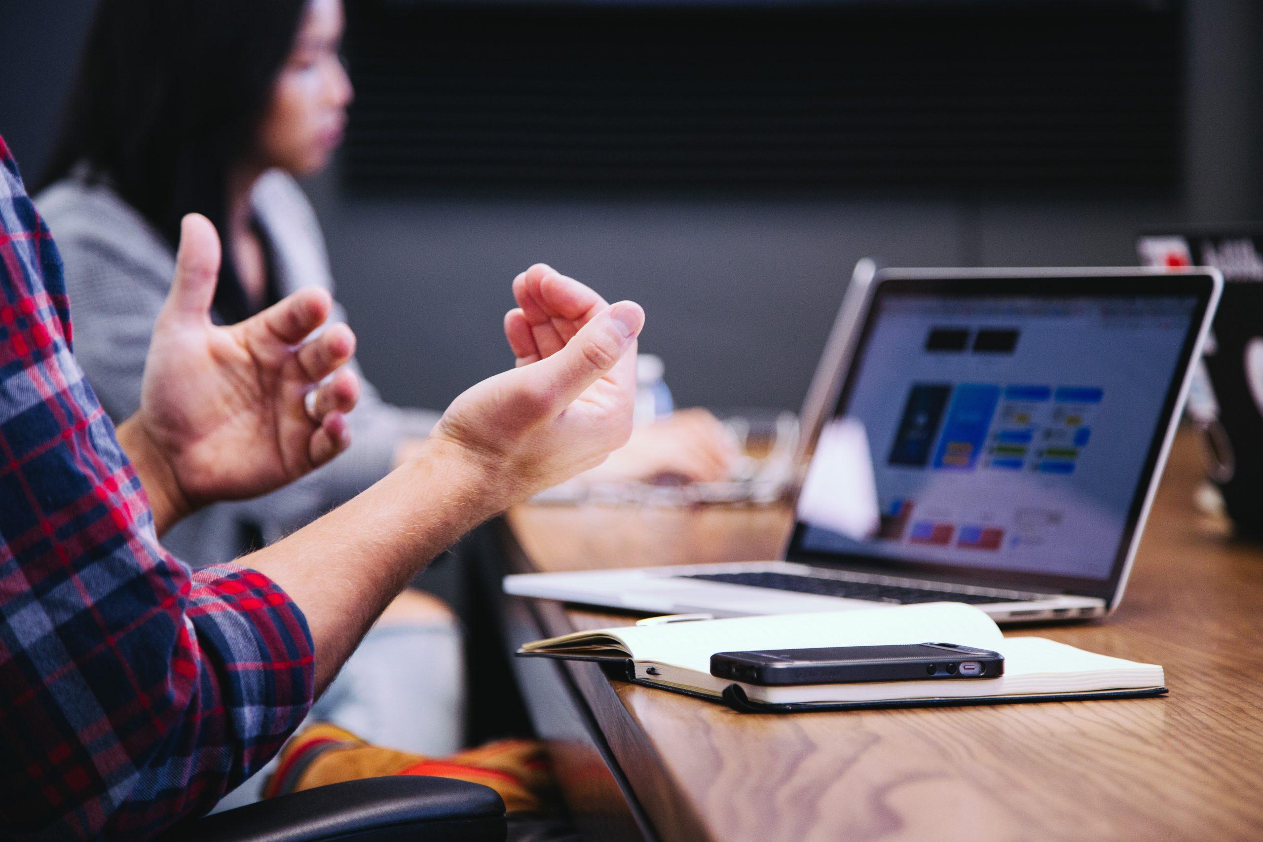 Overleggende collega's achter een bureau met een laptop en rekenmachine